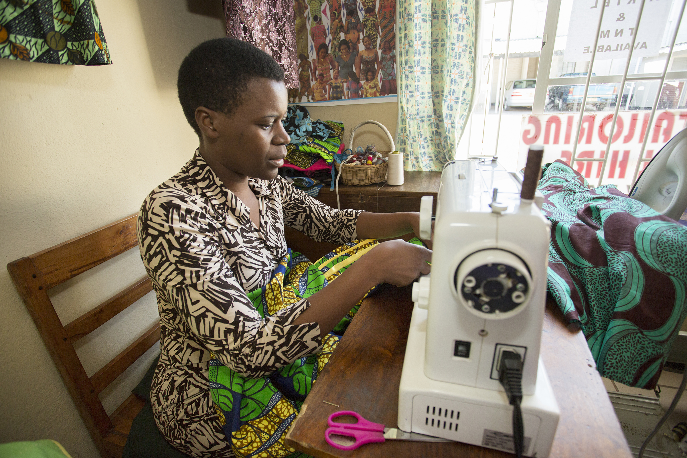 Photograph of Ivy at her sewing machine in her shop in Blantyre, Malawi.