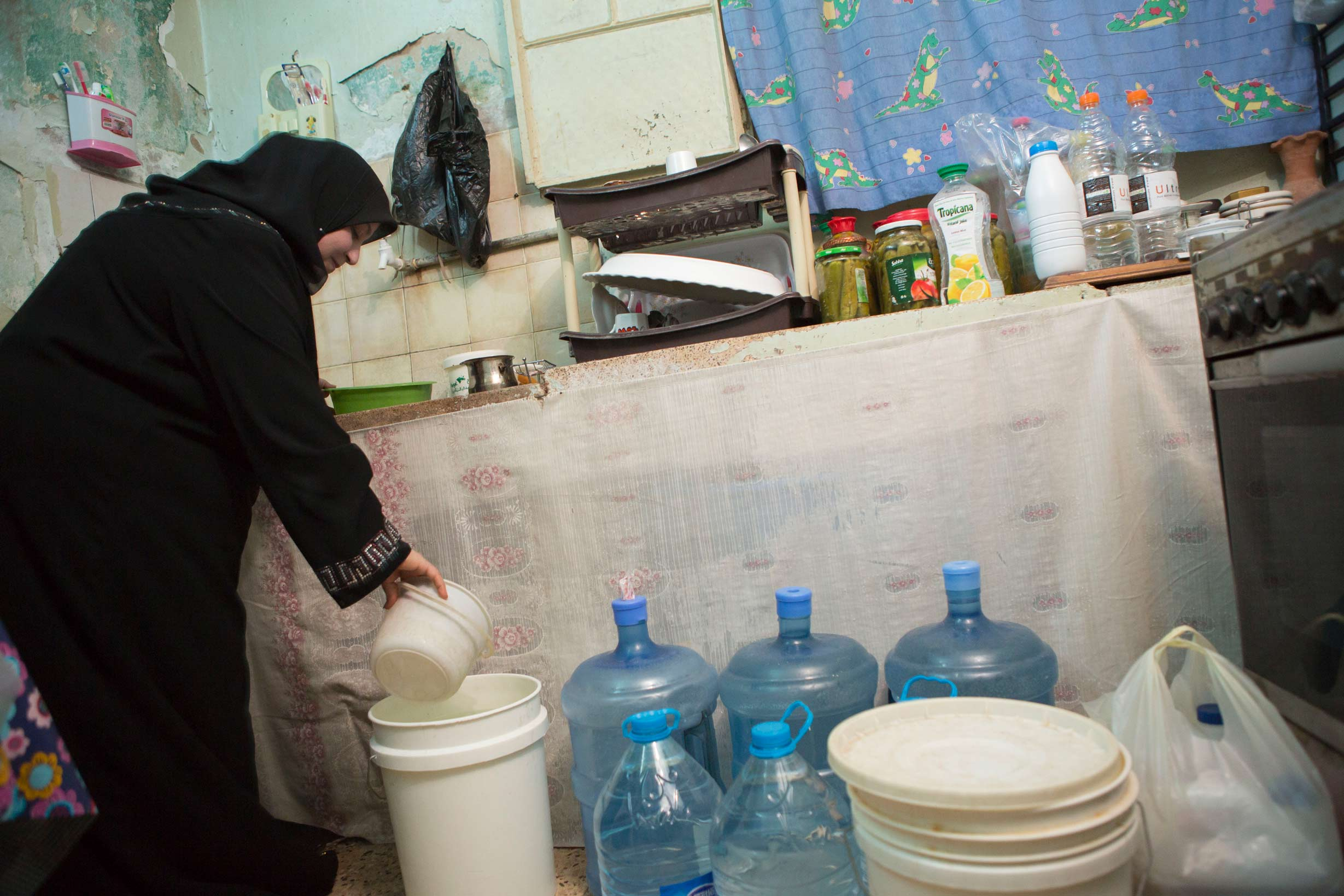 Mrs. Um Yazan Omran, a resident of Zarqa, Jordan, experiences water shortages. Here she is seen in her kitchen with several jugs of purchased water which she uses for the household.