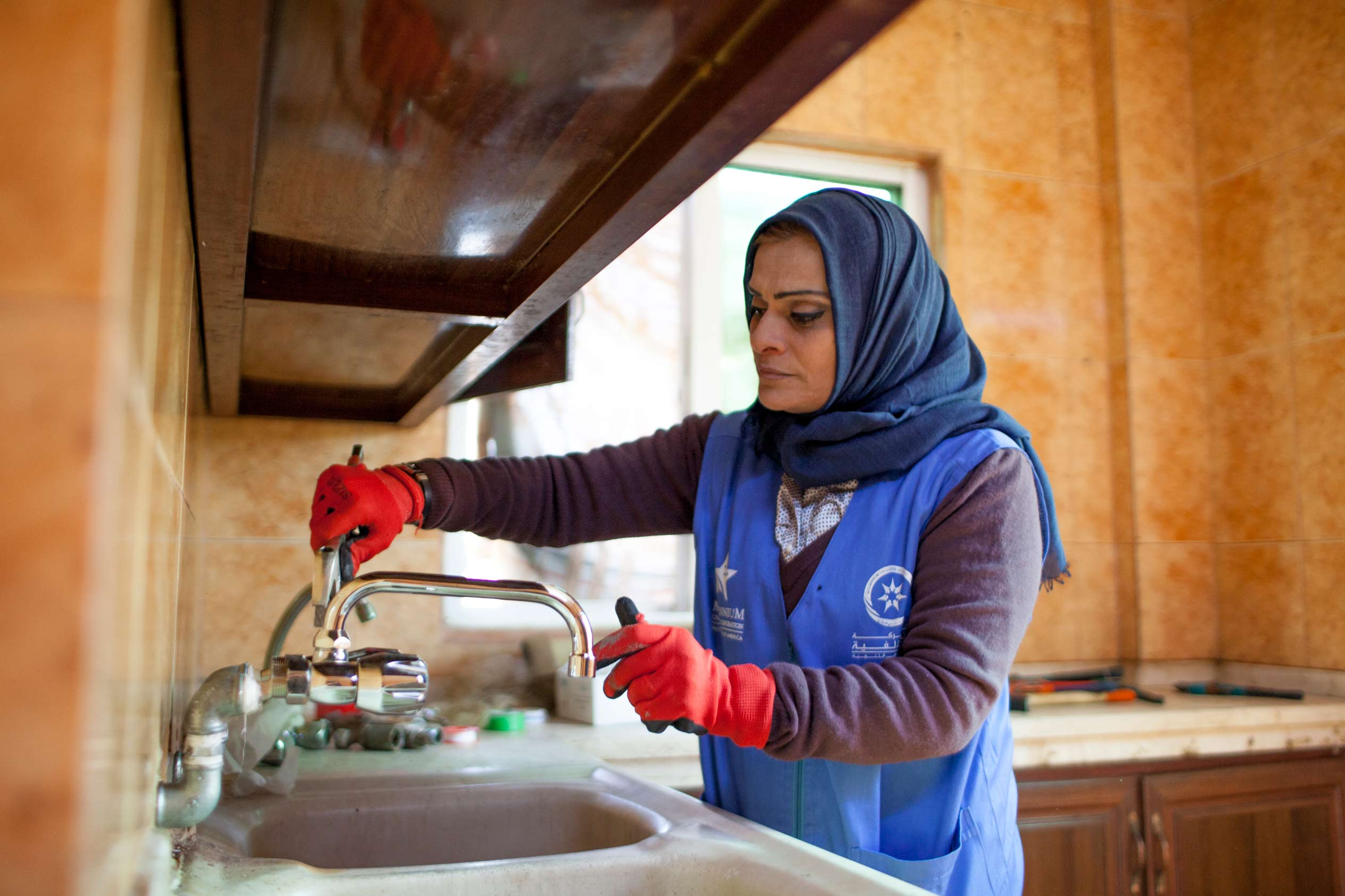 Photo: Ra'eda, pictured fixing a kitchen sink in Zarqa, Jordan, is one of 30 women who received training to become plumbers through a project that taught women how to effectively manage limited water resources in Zarqa, Jordan as part of MCC's Jordan Compact.