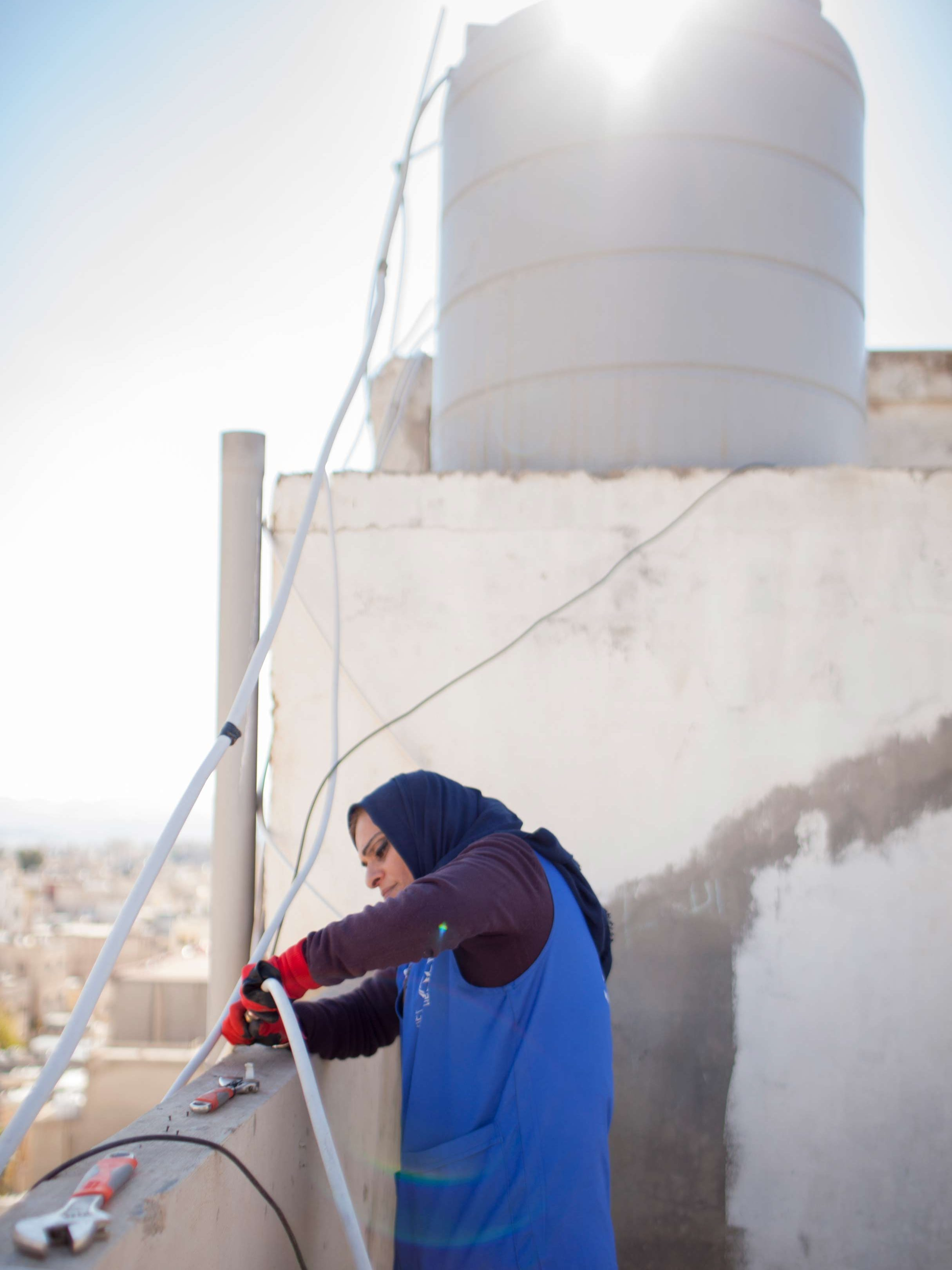 Photo: Ra'eda, pictured fixing a water connection on a roof in Zarqa, Jordan, is one of 30 women who received training to become plumbers through a project that taught women how to effectively manage limited water resources in Zarqa, Jordan as part of MCC's Jordan Compact.