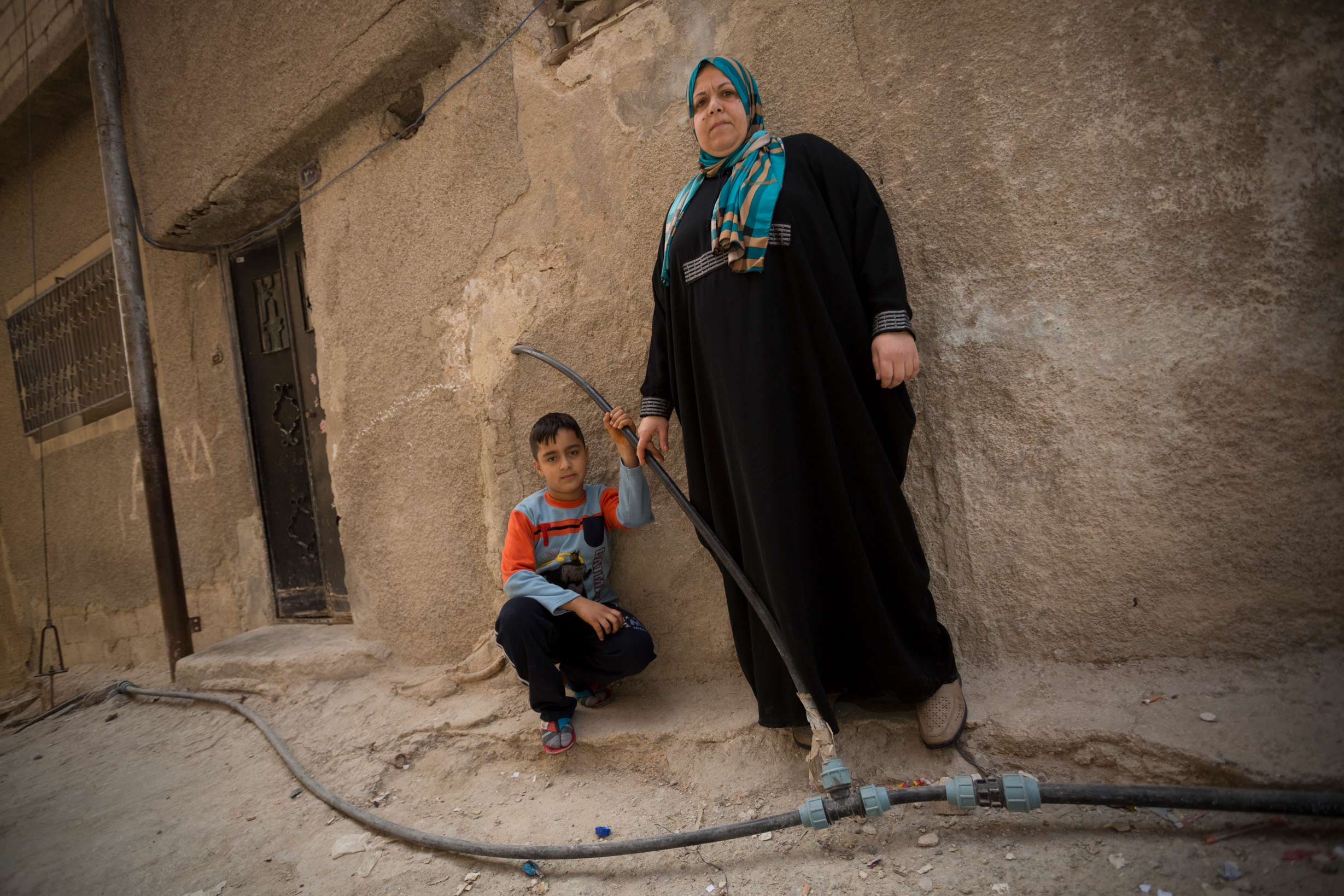 Mrs. Um Osama Omran and her son Sari stand among exposed municipal water pipes outside their home in Zarqa, Jordan in 2013. As part of a $275 million compact with Jordan, which closed in 2017, MCC has rehabilitated Zarqa's antiquated drinking and wastewater network and helped to expand a new wastewater treatment facility, all of which increased available water for drinking and irrigation and improved the safety and living conditions of the city's residents.