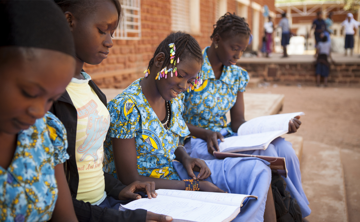 A photo of Yanta (second from right) stuyding with friends in the courtyard of their school, which was improved through the BRIGHT 2 Schools project in MCC's Burkina Faso Compact