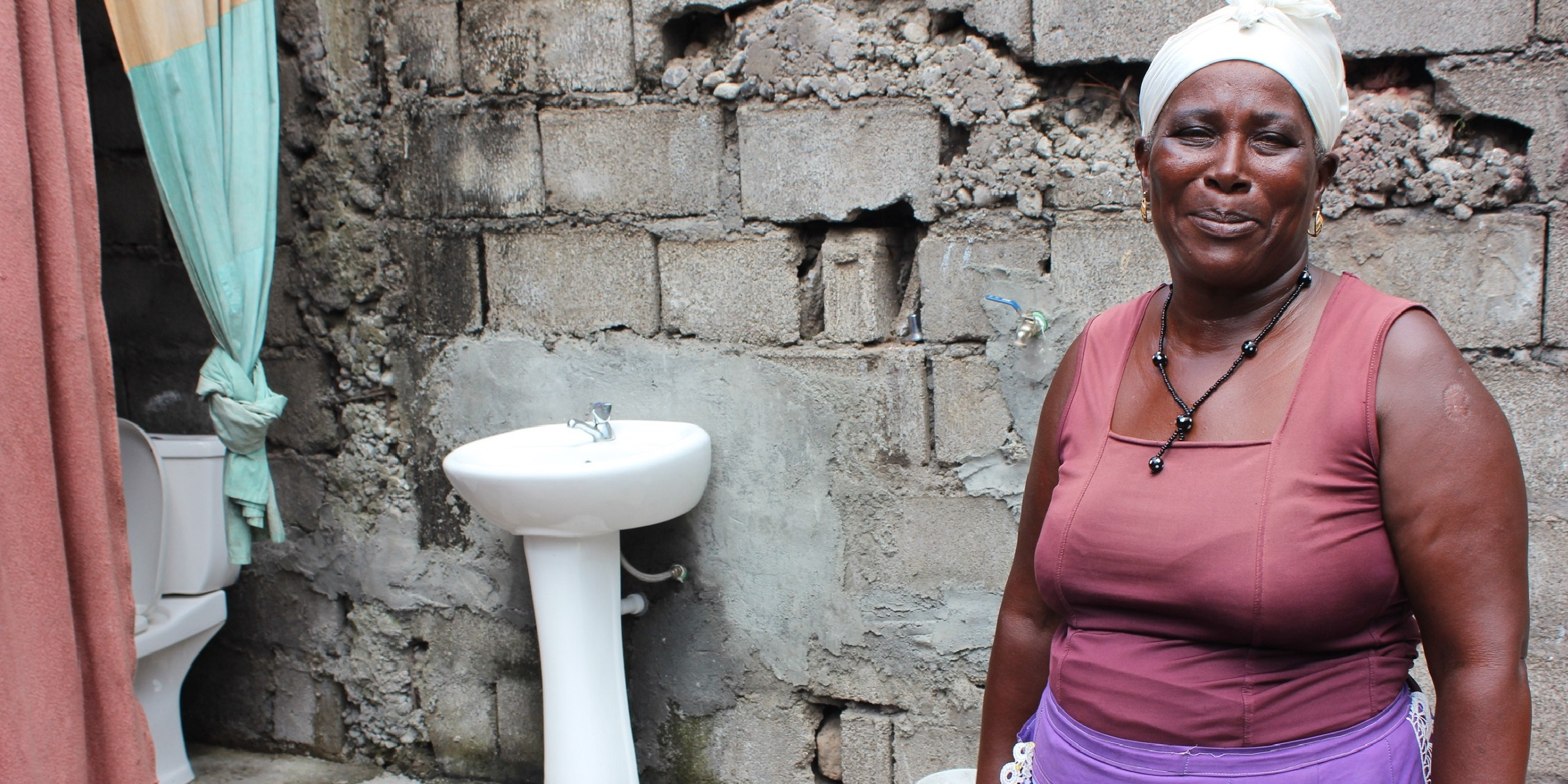 Celestina, an MCC beneficiary in Cabo Verde, stands next to her home where she now has indoor plumbing thanks to MCC's compact.