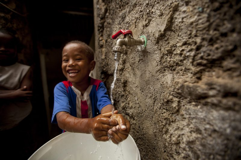 A boy in Cabo Verde enjoys running water in his home, set up as part of MCC's compact in the country.