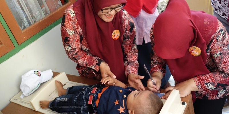 Health workers measure a baby boy at an MCC-funded community health center in the West Java region of Indonesia.