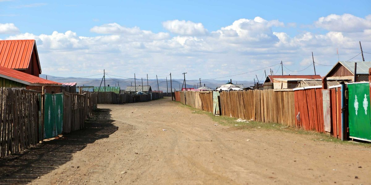A dirt road in Mongolia with houses on either side.