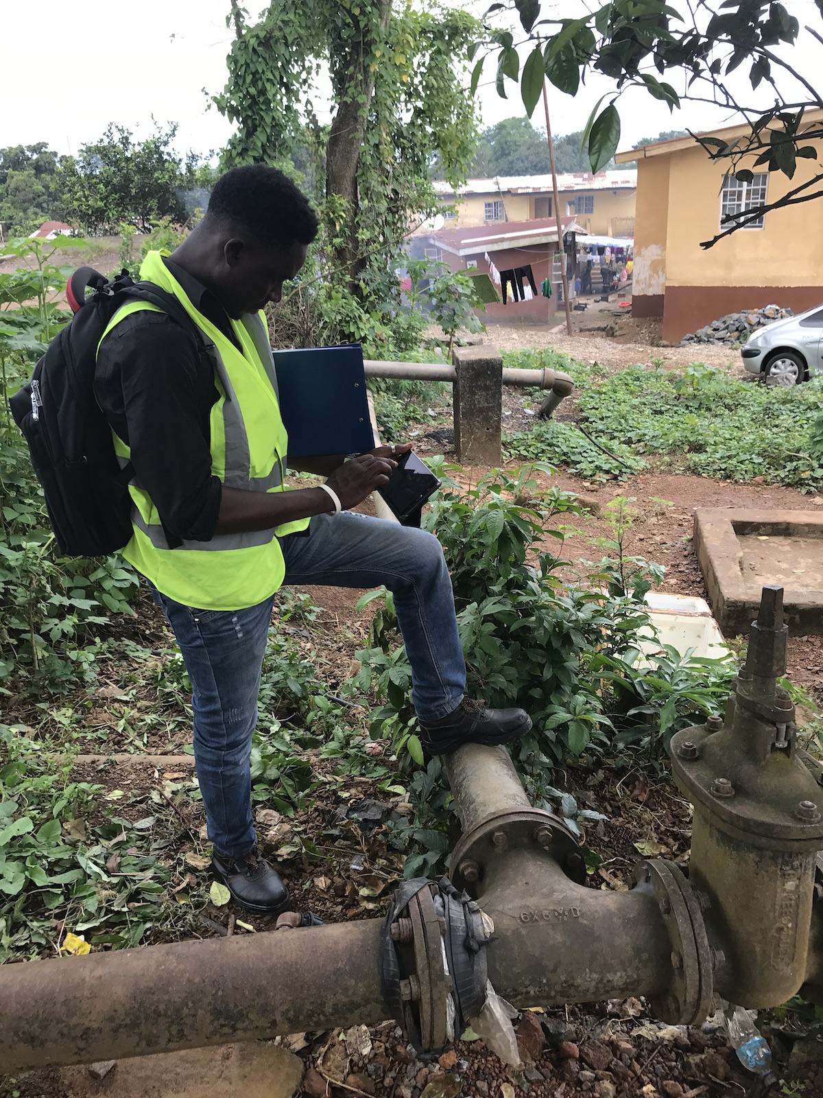 Technician Dennis Koroma maps water pipes, many of them exposed, in Freetown, Sierra Leone.