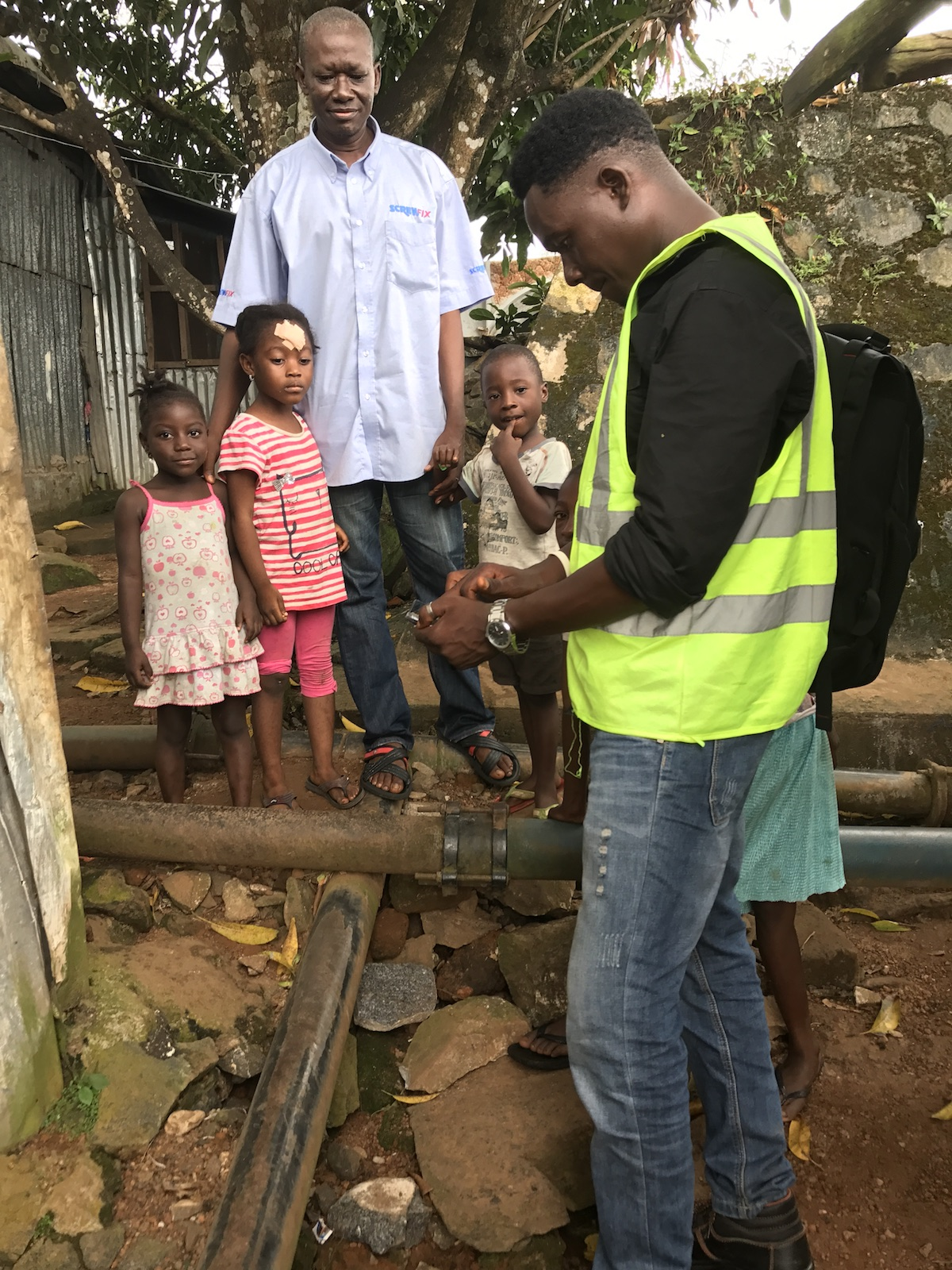 A family looks on as technician Dennis Koroma maps water pipes in Freetown, Sierra Leone.