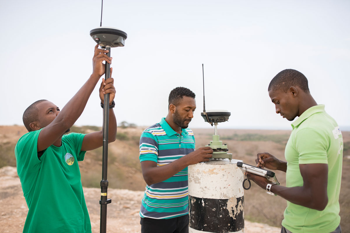 Photo of three men in Cabo Verde working to survey and geomap a property on the island of Maio as part of the MCC-Cabo Verde Compact for the purposes of clarifying land parcel rights and boundaries.
