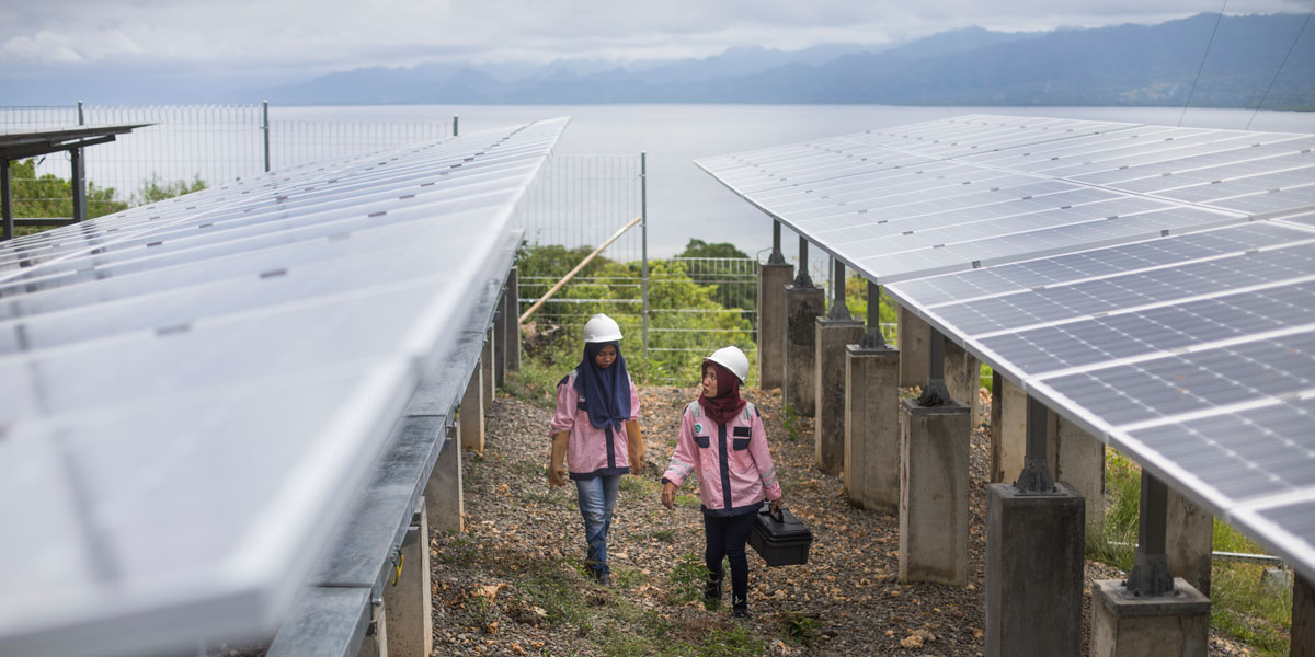 Photo of two women solar technicians in Indonesia walking between rows of solar panels.