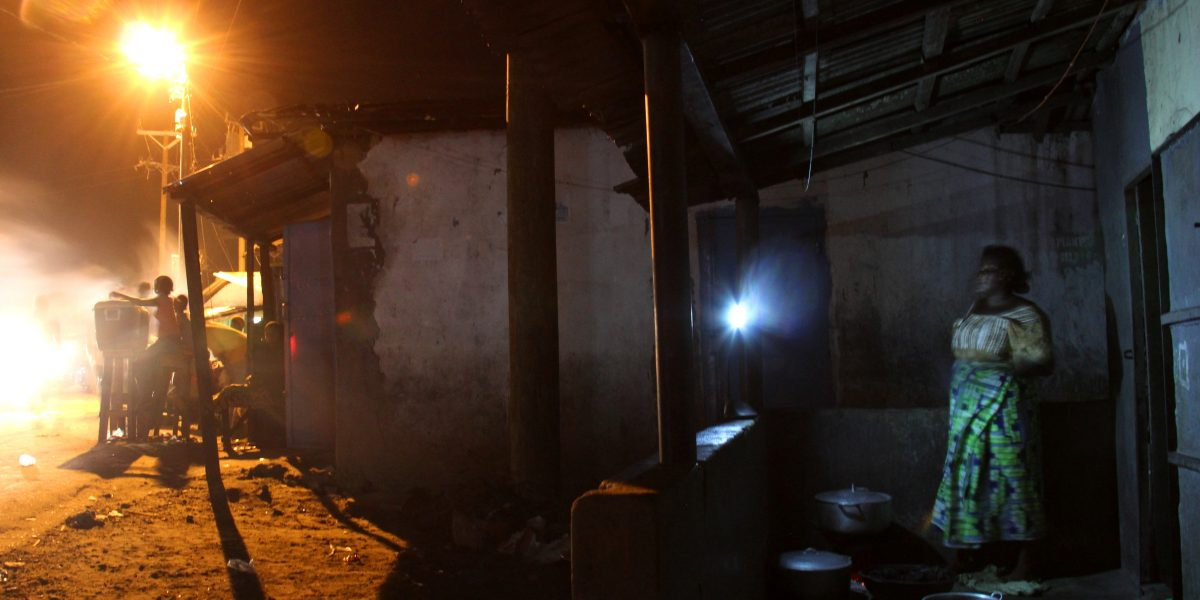 A woman cooking outside in the dark by flashlight in Monrovia, Liberia.