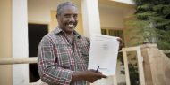 Manuel Gomes holds his newly acquired land title outside his home on the island of Maio, Cabo Verde. Mr. Gomes was able to obtain his title as a result of investments made as part of the MCC-Cabo Verde Compact that helped clarify land rights across the island nation.