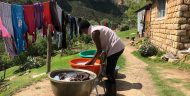 A photograph of a young woman doing laundry in front of her home on a mountainside in Morija, Lesotho. Three large tubs full of water are set on chairs in front of her for soaking, washing, and rinsing, with a line full of drying clothes in front and mountains in the background.