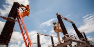 Workers servicing a substation financed by the compact.