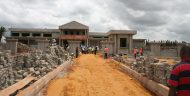 Construction workers look at a newly constructed courthouse in Benin.