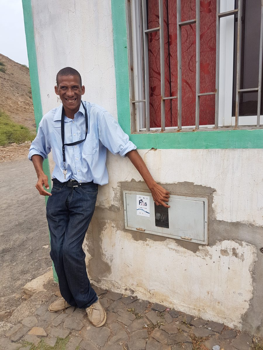 Jandir, a beneficiary of the MCC-Cabo Verde Compact, points to a water meter for his home on the island of São Vicente. Jandir organized his neighbors to help clear trenches for water pipes that were laid in their community.