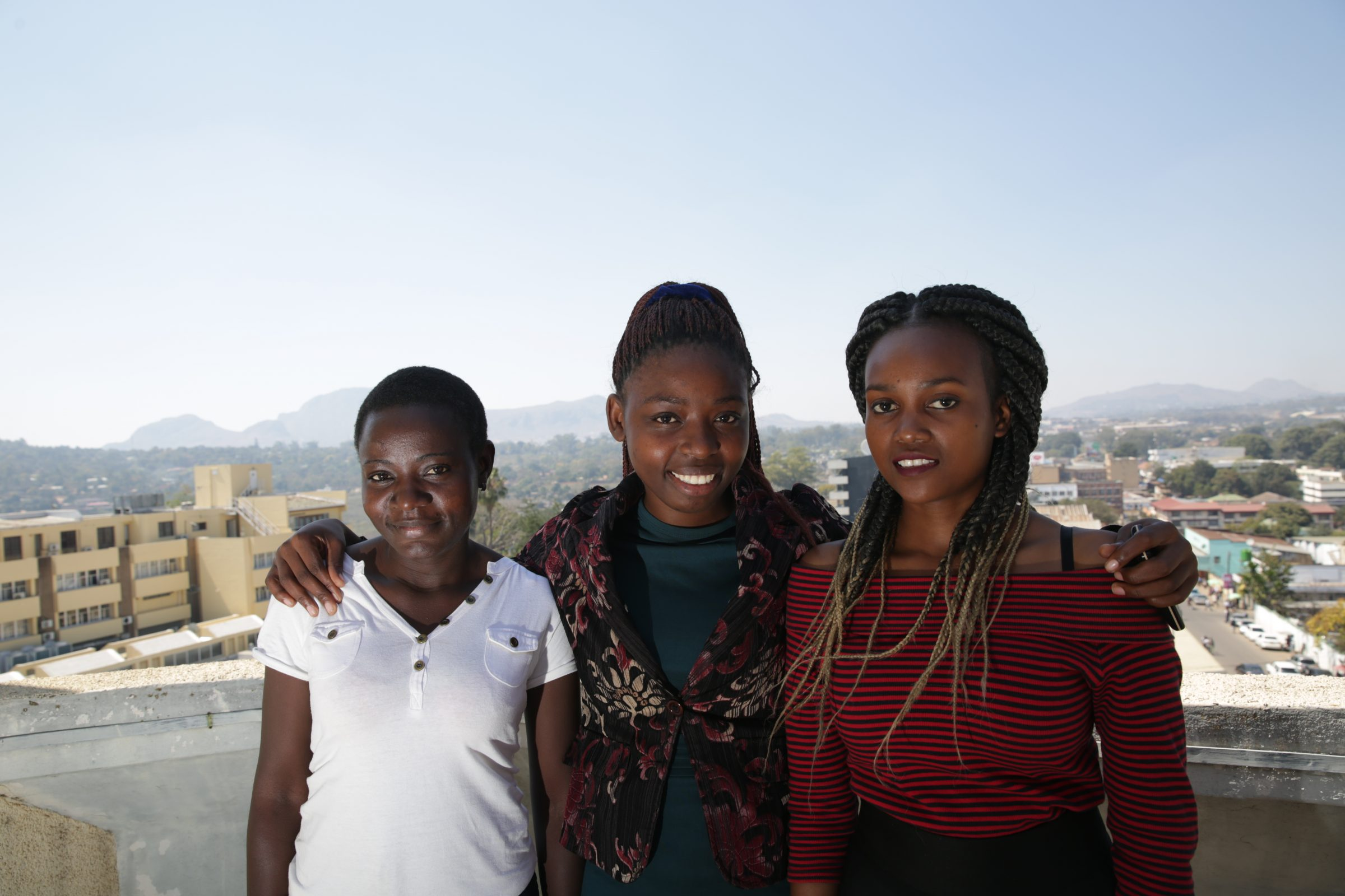 Photograph of three scholarship recipients posing together on the roof of ESCOM's Blantyre office
