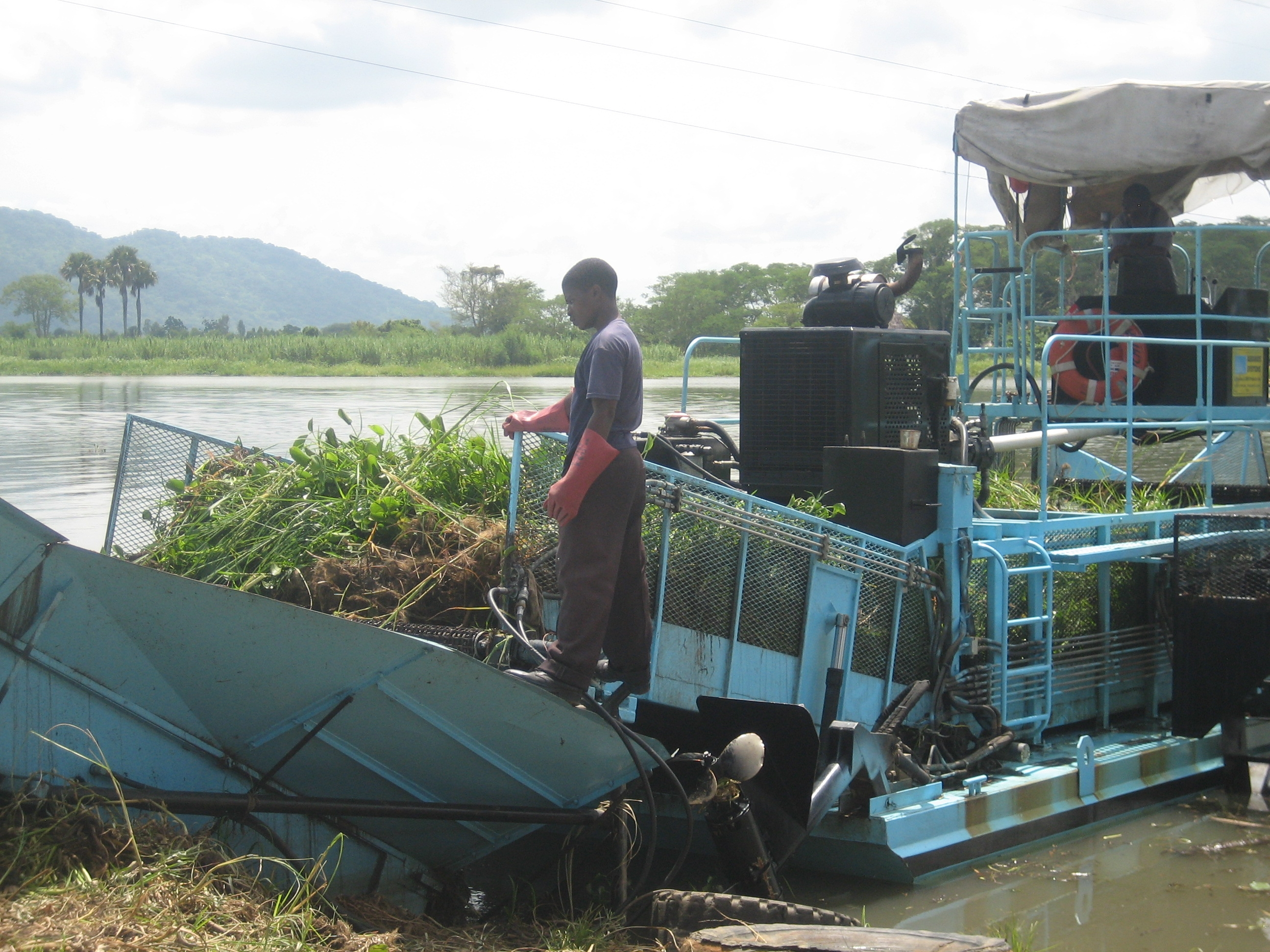 A two-man crew operates a weed harvester on the Shire River in Malawi to keep the hydroelectric plant from being damaged by over growth.