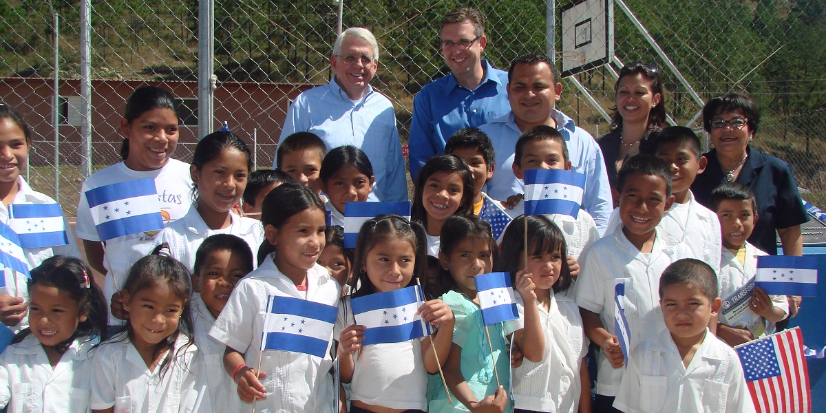 Jonathan Nash (back row, center) celebrates the opening of an MCC-funded school alongside students and Honduran government officials in Colonia Las Pumas in 2011.
