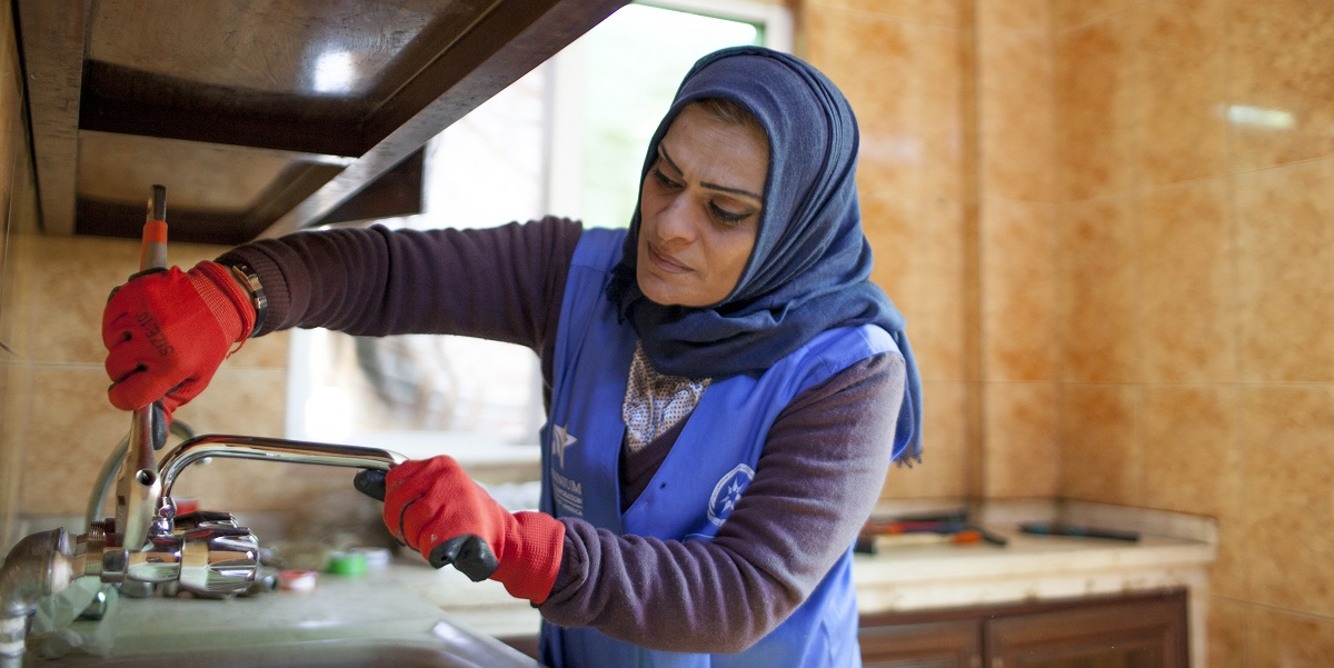 Ra'eda, one of 30 women trained as plumbers as part of the MCC-Jordan Compact, fixes a client's faucet in the city of Zarqa. Ra'eda and her colleagues are challenging attitudes about women's roles and professions in Jordan, which has one of the lowest women's labor force participation rates in the world.